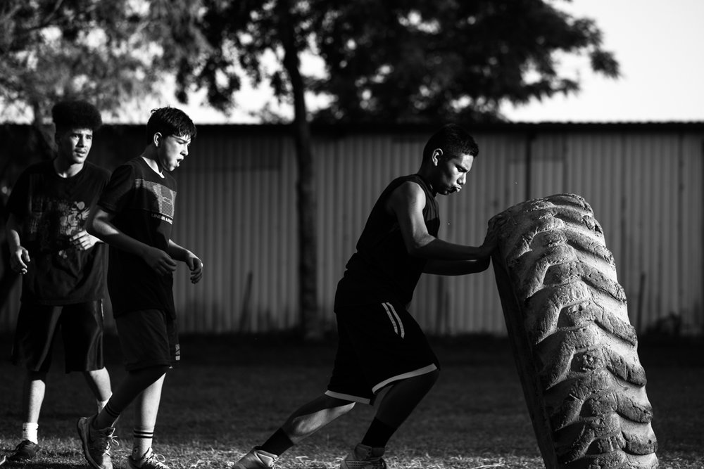 Edward Guitron, 15, lifts a tire in a team racing drill at the Ramos Boxing Gym in San Antonio, Texas on April 19, 2017. Athletes on the youth team train for three hours a day, six days a week.