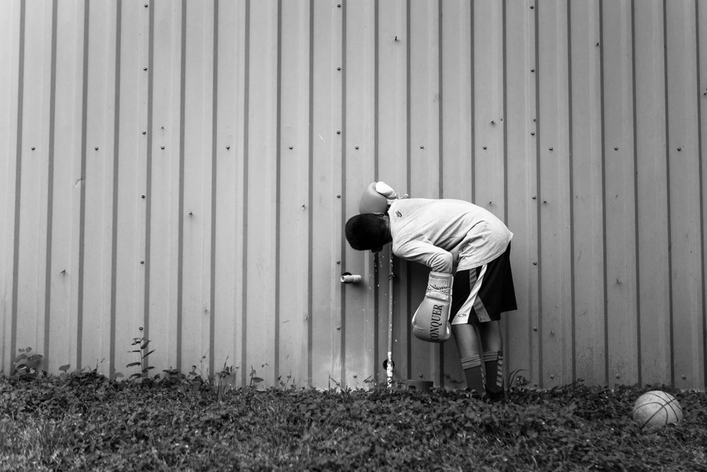 Between drills, an amateur boxer of the Ramos Boxing Junior Olympics team drinks water from an exterior spigot of the Ramos Boxing Gym in San Antonio, Texas.