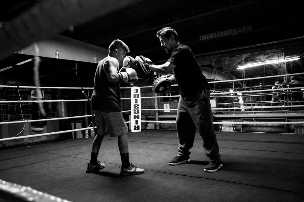 "After the day's training drills are complete, AJ Ramos, 13, goes through punching exercises with his father and owner of Ramos Boxing, Arturo Ramos III. The younger Ramos is currently ranked #5 in the nation for the 13- to 14-year-old 85-pound division. I didn't use to believe that talent could be genetic until I had a son,"" Ramos III said. ""He hits with a heavy hand, just like I did when I was younger."""