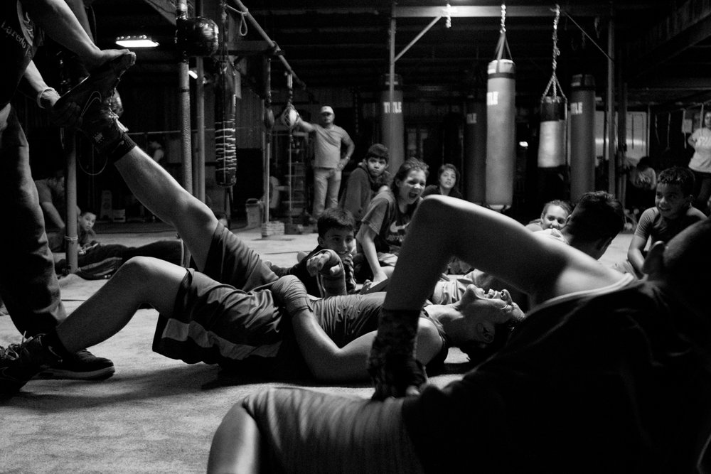 "Owner and head coach of Ramos Boxing gym, Arturo Ramos III stretches out the leg of Angel Colundres, 16,  after his thigh cramps up during a plank drill on April 19, 2017. ""I box mainly because it helps you release pain and stress in a good way,"" Colundres said."