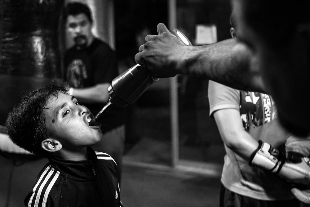 "Miguel Ángel Jacobo Jr., 9,  drinks water during a break between punching bag drills. Jacobo has only recently been registered as an amateur fighter though he has been boxing since age six. ""I get pretty nervous when I'm in the ring,"" Jacobo said. ""But I want to be professional when I get older."""