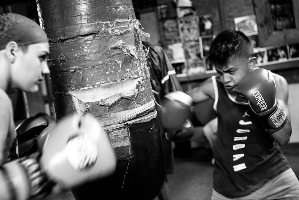 "Reina Tellez, 14, and AJ Ramos, 13, take turns punching  during a bag drill at the Ramos Boxing gym in San Antonio, Texas. ""Boxing has showed me more discipline,"" Tellez said. ""You have to work to win and be successful."" Lynda Gonzalez/Reporting Texas"