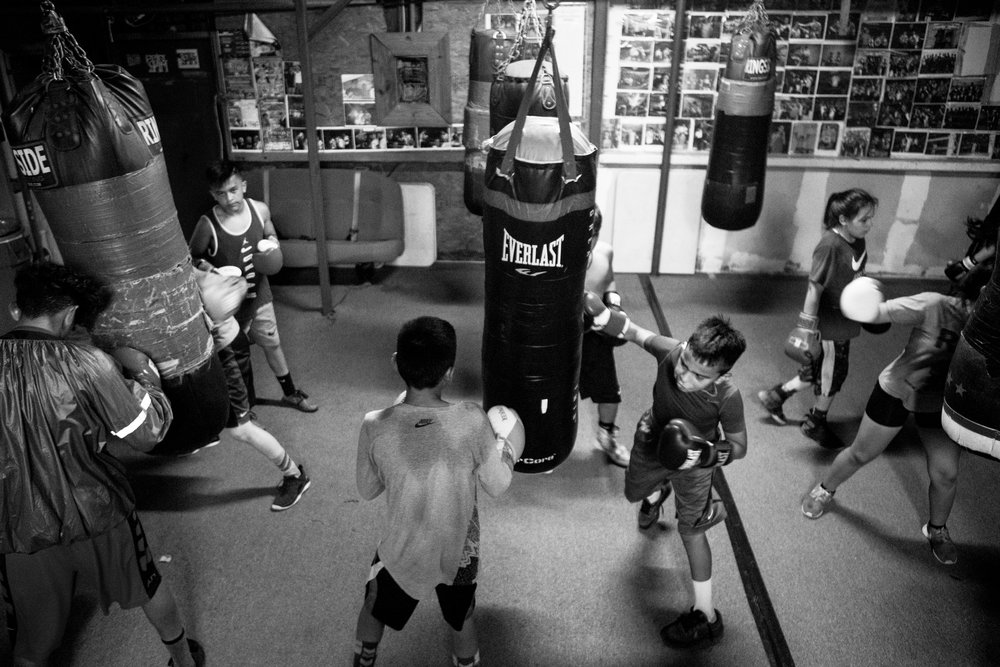 "Victor De Los Santos Jr., 12, center, punches a bag at the Ramos Boxing gym with other members of the Junior Olympics team. Many of the young athletes devote hours in the gym to continue a family tradition they say ""runs in their blood."""