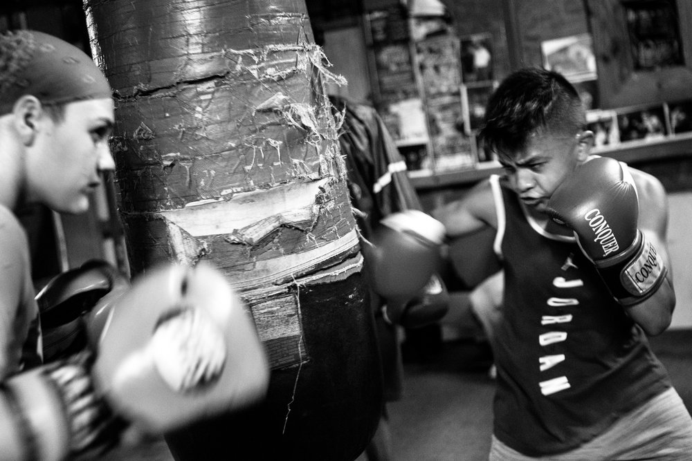 Reina Tellez, 14, and AJ Ramos, 13, take turns punching during a bag drill at the Ramos Boxing gym in the South Side neighborhood of San Antonio, Texas.