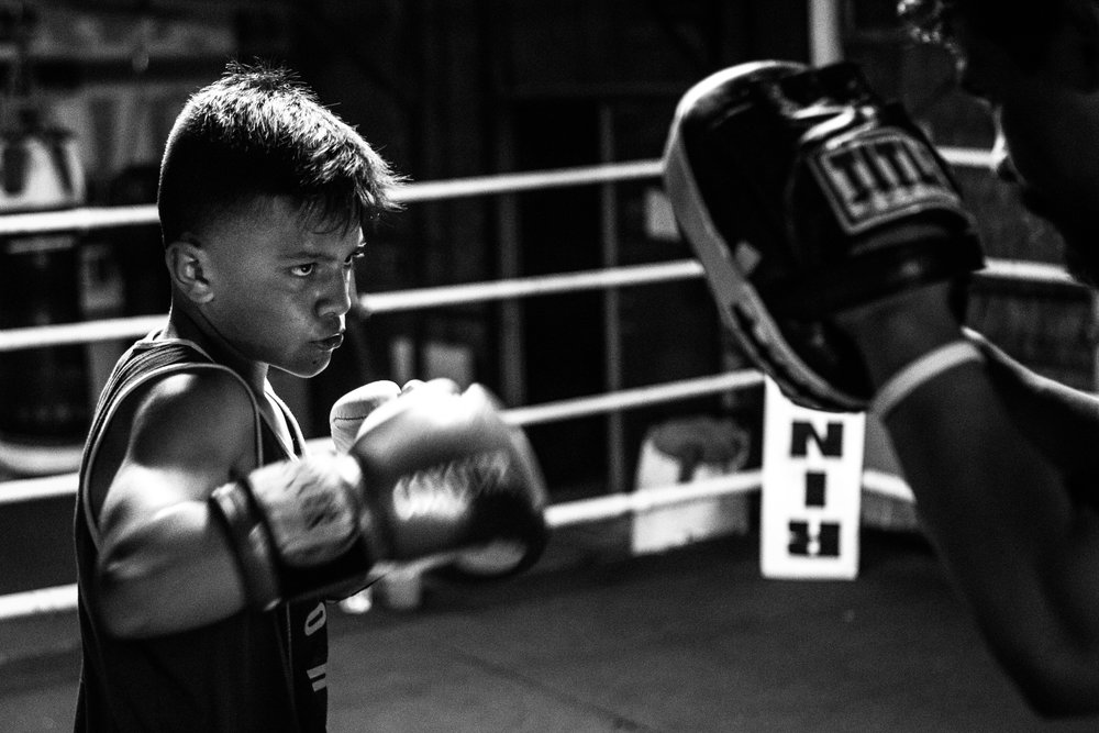 After the day's training drills are complete, AJ Ramos, 13,  goes through punching exercises with his father and owner of Ramos Boxing, Arturo Ramos III. The younger Ramos is currently ranked #5 in the nation for the 13- to 14-year-old, 85-pound division.