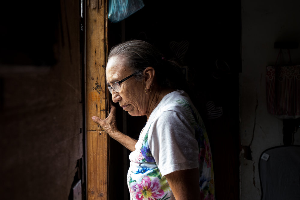 Teresa de la Zoya, 69, looks out the back door of her mobile home located in the border colonia of Indian Hills, Texas. Her home lacks centralized air conditioning in a place where summer temperatures usually rise above 100 degrees.