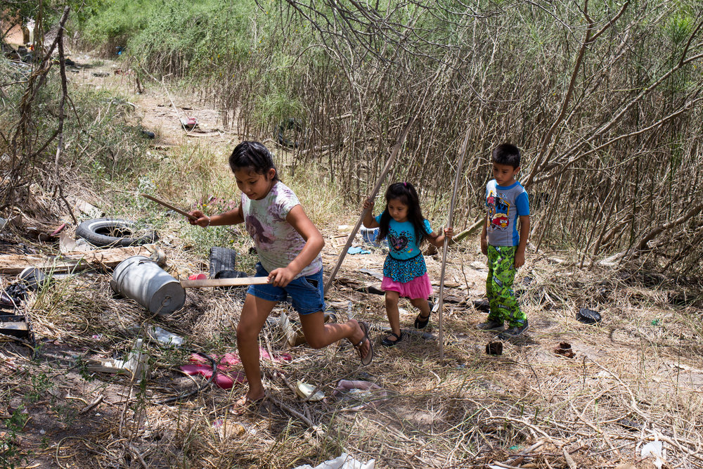Alondra, Ashlee, and A.J. play in the property behind their grandmother's home along the Texas-Mexico border. The children live in a colonia — a type of informal settlement that floods often and lacks a combination of electricity, paved roads, water and sewage systems. Approximately half a million low-income, immigrant Latinos live along the Texas-Mexico border in almost 3,000 colonias.