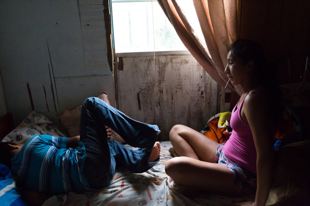 Teresa's grandchildren, Jennifer and Uriel, rest from the heat in a bedroom of the family's mobile home.