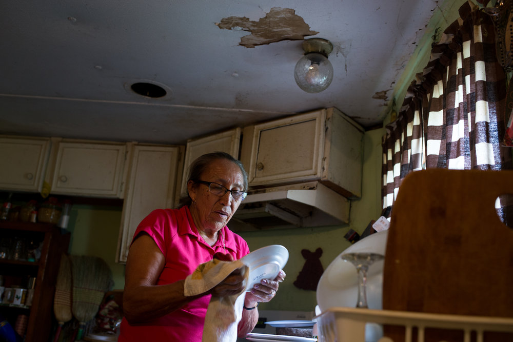 Teresa washes dishes after feeding her grandchildren lunch. Heavy rains and floods each year have damaged the ceiling, foundation and floors of the mobile home Teresa bought 18 years ago for $8000. She said she wouldn't be able to afford monthly payments for a new house, even if local non-profits could offer one at a low monthly rate.