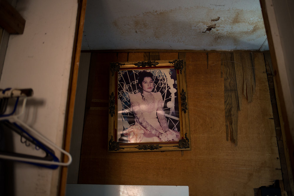 A photograph of Teresa's daughter hangs in a visibly water-damaged hallway.
