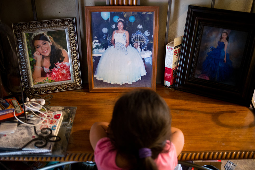 Ashlee, 4, looks at photos of her mother and other female relatives at their quinceañeras, a fifteenth birthday celebration commonly celebrated among Mexicans and Mexican-Americans along the border. Ashlee's mother works as a full-time medical assistant, relying on her Teresa to watch her four children during the summer since they cannot afford childcare.