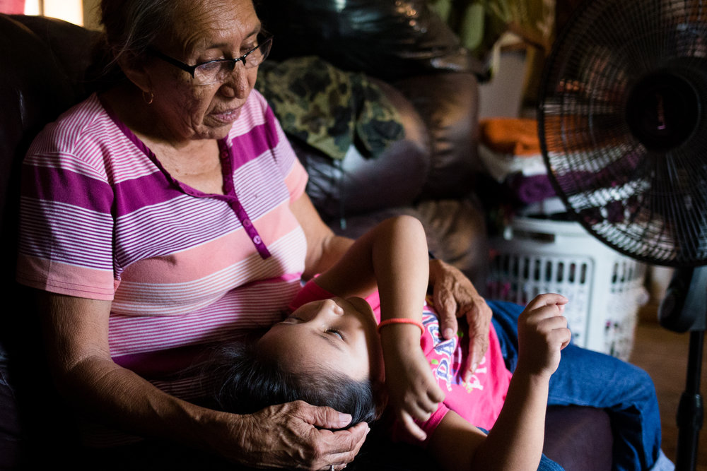 Teresa and her grandchild, Ashlee, rest for a moment by one of three fans used to keep the heat at bay in their poorly insulated mobile home. Teresa quit her job as a home care provider to care for her children, but she and her adult daughter struggle to pay utility bills as a result.