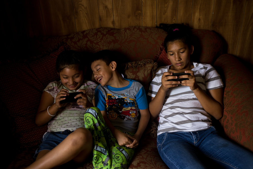 Three of Teresa's grandchildren, Alondra, A.J. and Jennifer, play games on their disconnected cell phones. Their favorite game to play is Minecraft, which allows players to build their own dream homes.