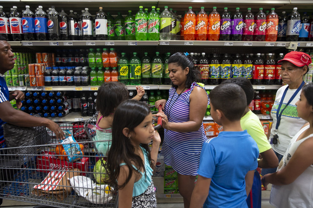 Rosales buys snacks at an H-E-B grocery store with family members to prepare for a family trip to the San Marcos River on Thursday, June 28, 2018.