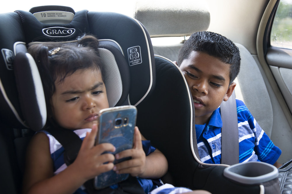 David Rosales, 11, watches his 2-year-old sister, Kelly, play with his mother's phone as they drive to a doctor's appointment on Friday, June 22, 2018.