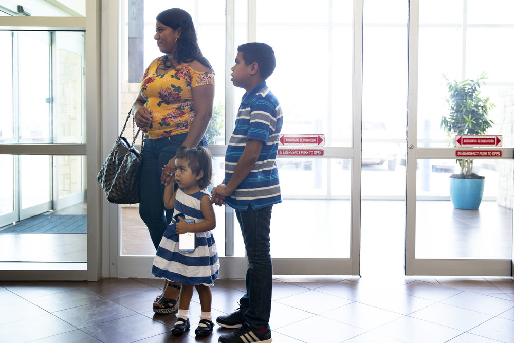 Lizeth Rosales, an asylum recipient from Honduras, stands in a health facility with her two children, David, 11, and Kelly, 2, in Kyle, Texas, on Friday, June 22, 2018.