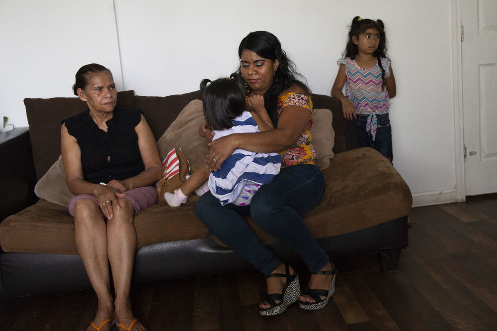 Rosales, an asylum recipient from Honduras, sits with her mother, Rosa, and her 2-year-old daughter, Kelly, in the living room of their mother mobile home in Kyle, Texas, on June 22, 2018.