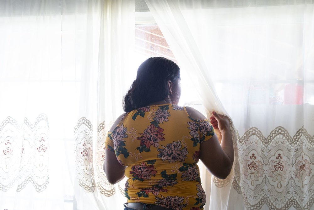 "Lizeth Rosales, an asylum recipient from Honduras, looks out the window at her mother's mobile home in Kyle, Texas, on June 22, 2018. Rosales recieved asylum in 2017 after experiencing domestic violence from her son's father. ""I get another chance at life here,"" Rosales said."
