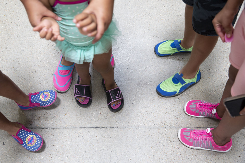 The nieces of Lizeth Rosales, an asylum recipient from Honduras, wear water shoes before a trip to the San Marcos river on Thursday, June 28, 2018.