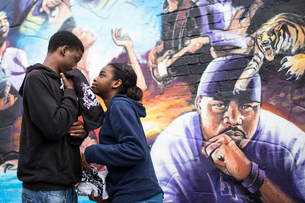 Octavis Berry Jr. and Krystal Berry take a moment to admire their father's portrait, left, during artist Chris Rogers' mural unveiling at 12th and Chicon streets on Feb. 17, 2018, in Austin, Texas. The children's father, Octavis Berry, was a local rapper who passed away in 2011.