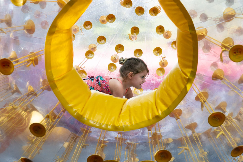 Evelyn Benton plays in an inflatable ball at the 5th Annual Austin Duck Derby on Saturday, Aug. 4, 2018. A dump truck poured nearly 20,000 rubber ducks from the Ann W. Richards Congress Avenue Bridge into Lady Bird Lake to raise money for the Austin Boys and Girls Club Foundation.