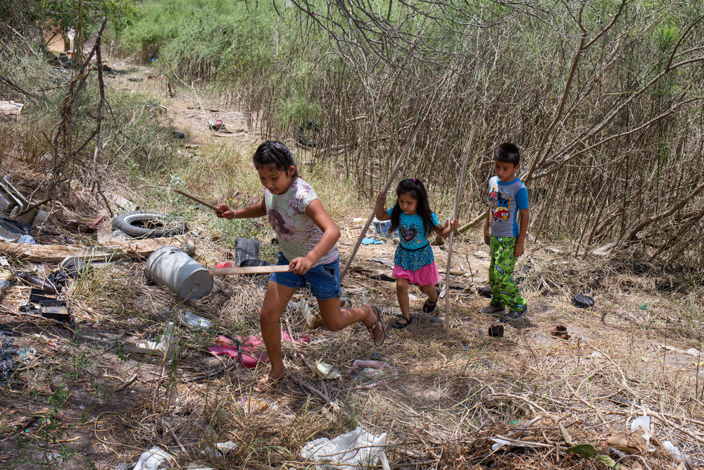 Alonda, Ashlee, and A.J. play in the property behind their grandmother's home along the Texas-Mexico border. The children live in a colonia — a type of informal settlement that floods often and lacks a combination of electricity, paved roads, water and sewage systems. Approximately half a million low-income, immigrant Latinos live along the Texas-Mexico border in almost 3,000 colonias.