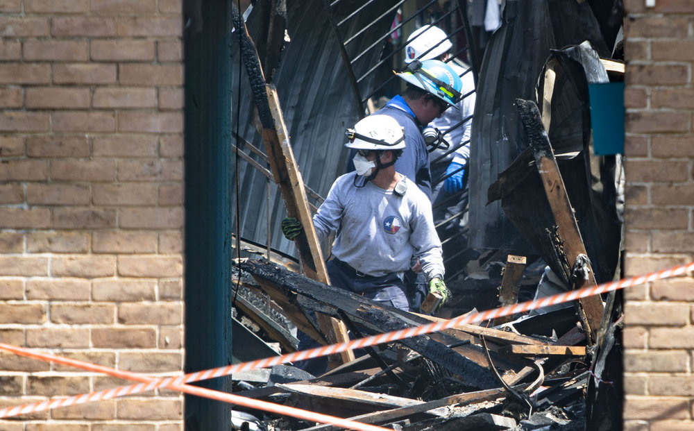 Emergency personnel continue search and recovery efforts at the Iconic Village apartments, where a fire broke out early Friday, in San Marcos, Texas, on Monday, July 23, 2018. Fire investigators recovered a fourth body from the rubble on Monday morning, San Marcos authorities said.