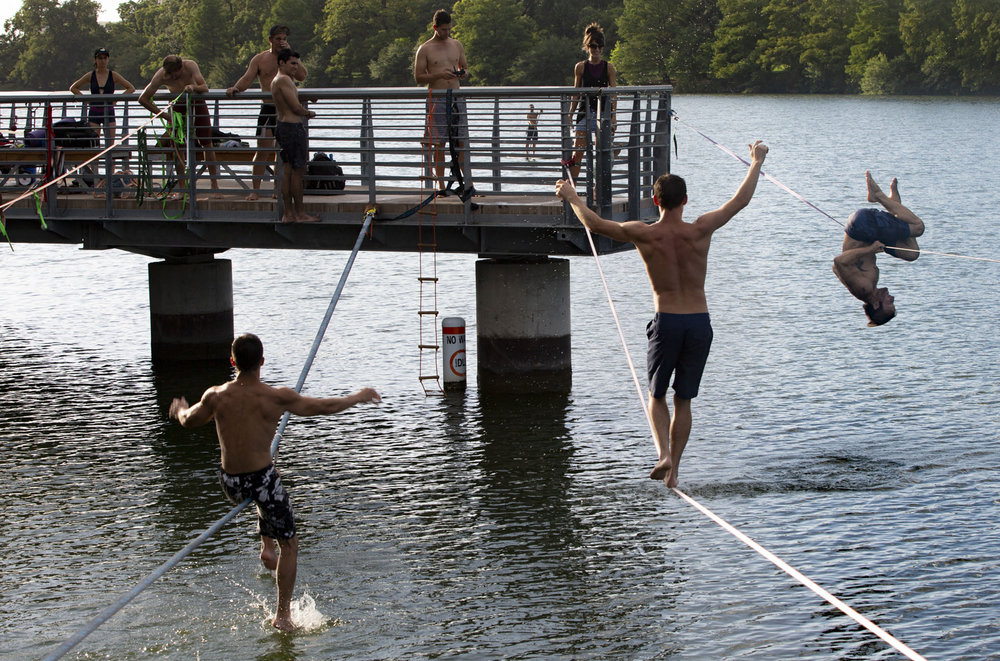 Slackliners jump and flip above Lady Bird Lake in Austin, Texas, in July 2018.