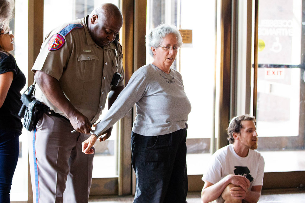Susan Lippman is arrested at the Texas Railroad Commission building while participating in the Texas Poor People's Campaign rally on Monday, June 4, 2018. About 60 people marched from the Texas State Capitol to the Texas Railroad Commission to demand lawmakers to ban oil and gas permits.