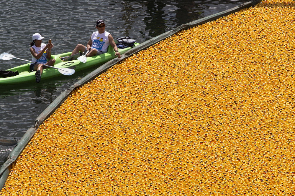 Spectators on Lady Bird Lake take photos of the nearly 20,000 rubber ducks dumped from the Ann W. Richards Congress Avenue Bridge into the lake as part of the 5th Annual Austin Duck Derby on Saturday, Aug. 4, 2018, in Austin, Texas.