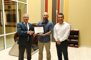 Philip Austin receives his AWG Employee of the Quarter Certificate. Pictured left to right: Yorktown CEO Bryan Dyer, Philip Austin, and Program Manager Jesse Cisneros