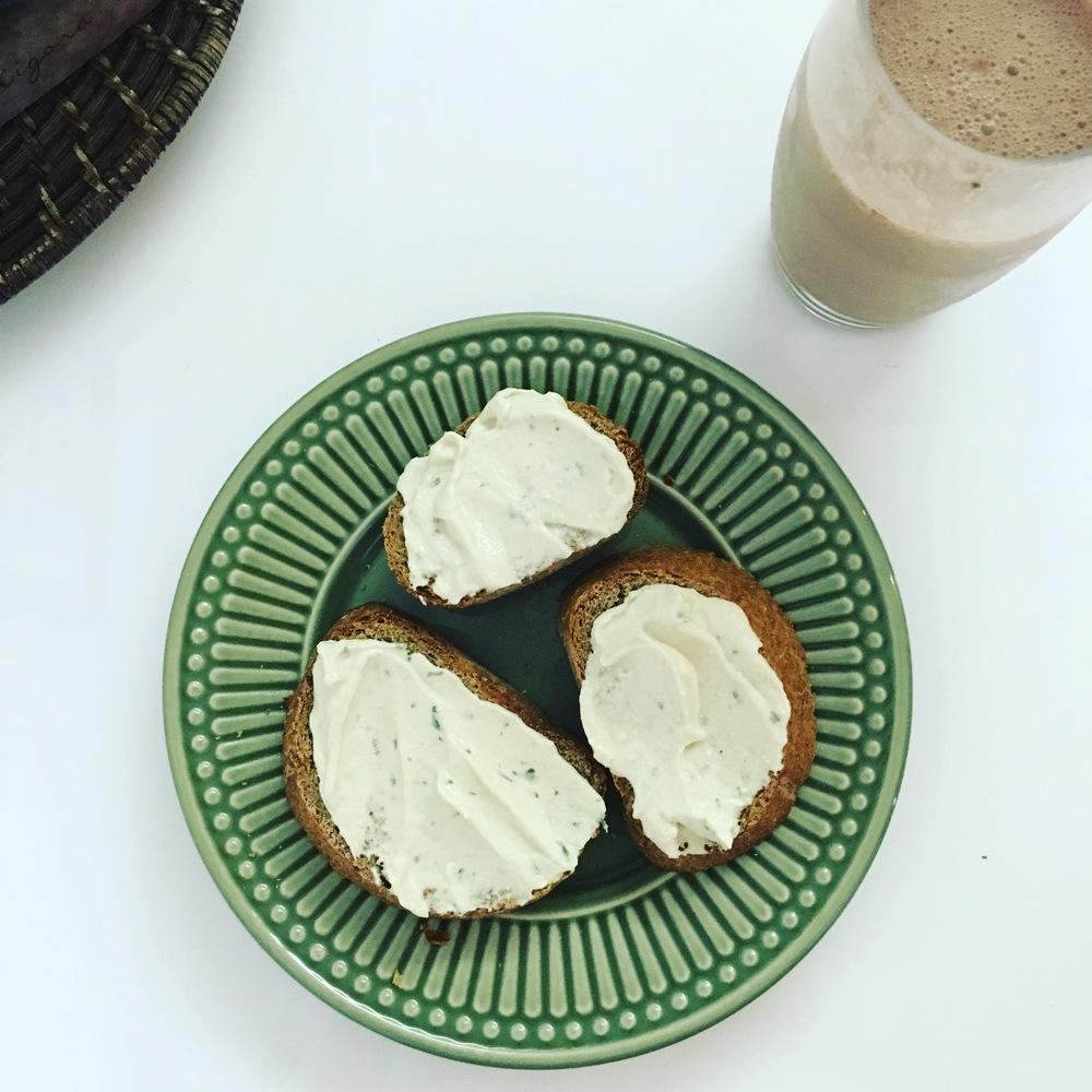 Pão sem glúten com pasta de leguminosas e leite vegetal com cacau em pó.