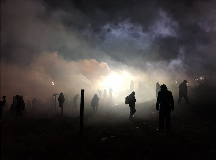 Water cannons and tear gas -- a chemical weapon banned from international conflict and many police  forces around the world since 1993 -- dispersed on water protectors camping out near the pipeline. Photo credit unknown to me, but if you have his/her information, please send it my way and I'll update the post.