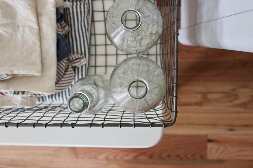 Clean out old vinegar bottles to fill with bulk liquids in a zero waste home | Litterless