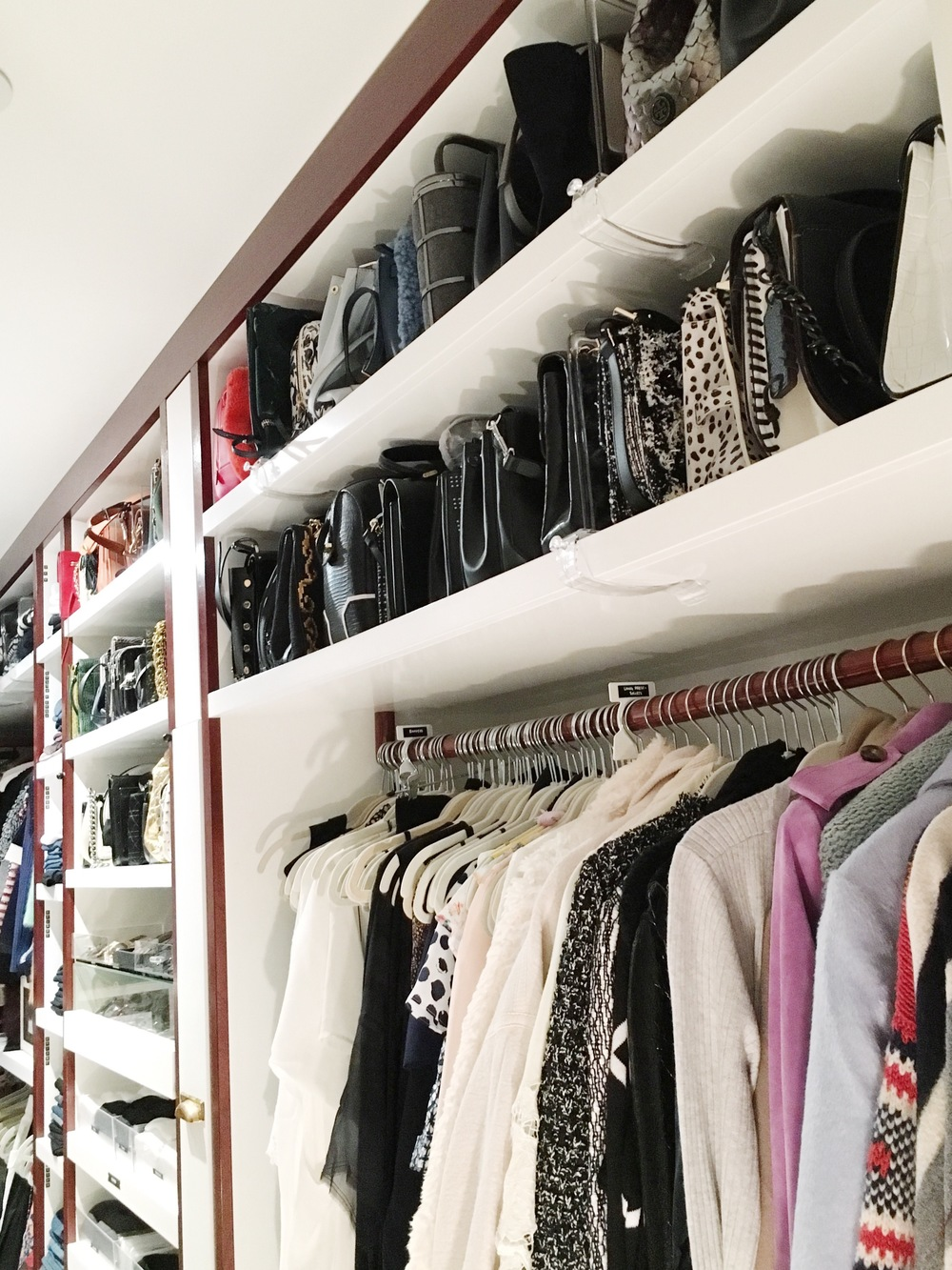 On the right: Coats and long dresses. The top shelf holds all the large purses organized by color and separated with acrylic shelf dividers.