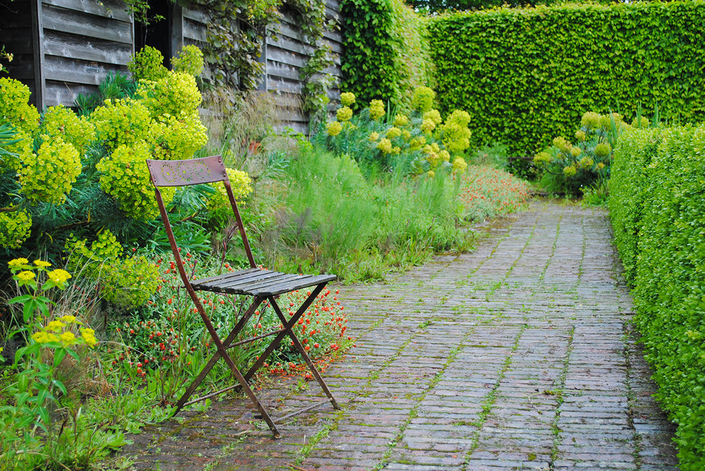 A lone chair sitting by the house beckons visitors.  But, no time to sit.  We must see more of the garden!
