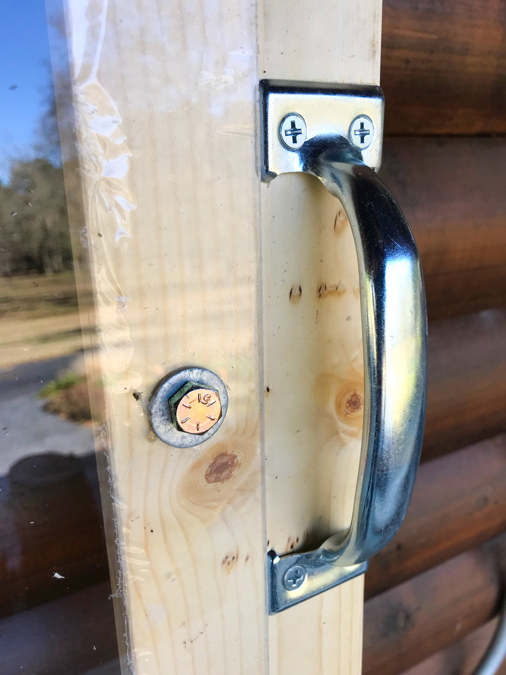 A bolt and washer hold the plexiglass on the wooden frame, and to the right is a handle for the light.