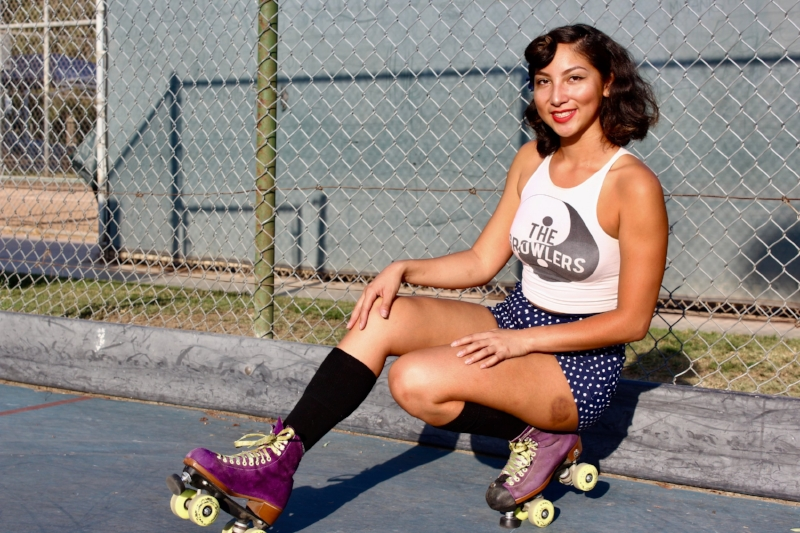 Killa has been skating for years and gravitates toward the classic vintage pin-up look on skates. Roller skating started in the '50s, and a lot of the fashion has inspired modern skaters. She's currently wearing the classic pin-up hair with flowers, the classic red lip and the high-rise shorts that embody that vintage look. Outside of the skates she has a more casual style, so this is a chance for her to dress up. Of course, where she skates impacts what she wears, but she does love the feeling of twirling on skates in dresses.