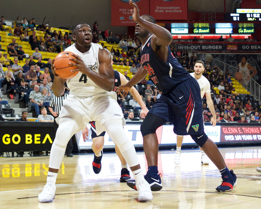 Long Beach State senior center Temidayo Yussuf (4) posting up against Fresno State's Terrell Carter II (34).  Credit: Long Beach State Athletics/John Fajardo