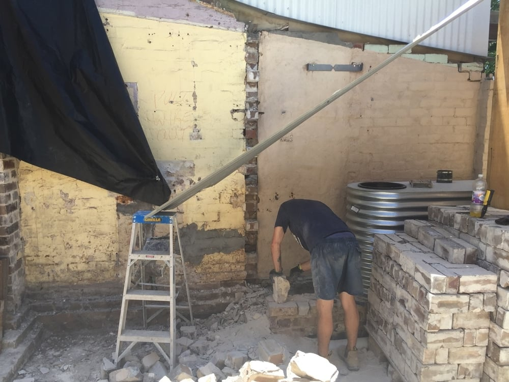 Andrew, a builder, recycling bricks and getting them ready for the bricklayer