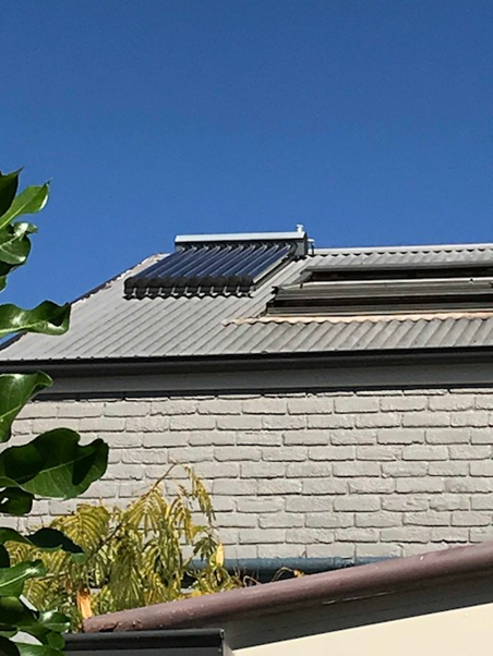 • Distant view of north-facing, roof-mounted evacuated glass solar hot-water collector (left of skylight) with 10 removable and replaceable tubes