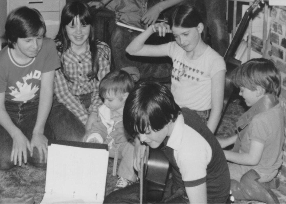 Patrick playing guitar, MacNeil Family, Ashley, Sutu, and Christopher 1981.jpeg