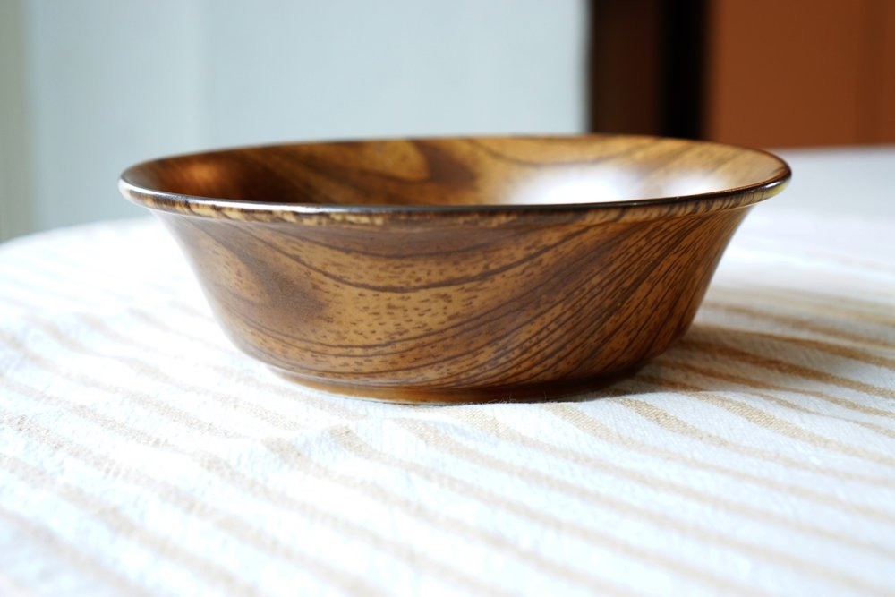 This is ceramic bowl however its distinctive pattern makes it appear wooden.  It is Microwave and Dishwasher safe!