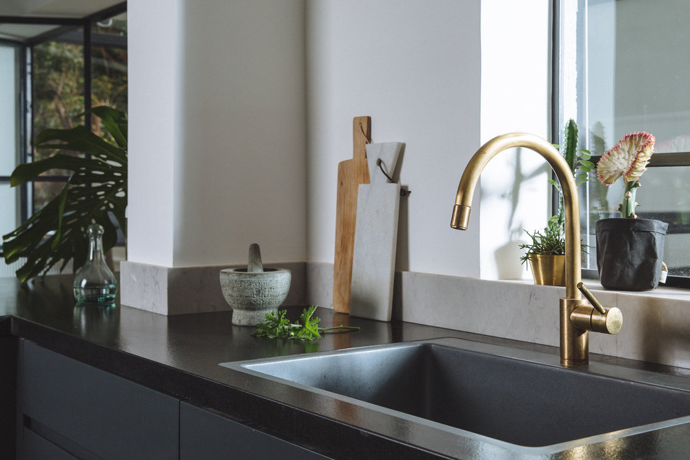Dark themed kitchen, minimalist and elegant. Brass faucet