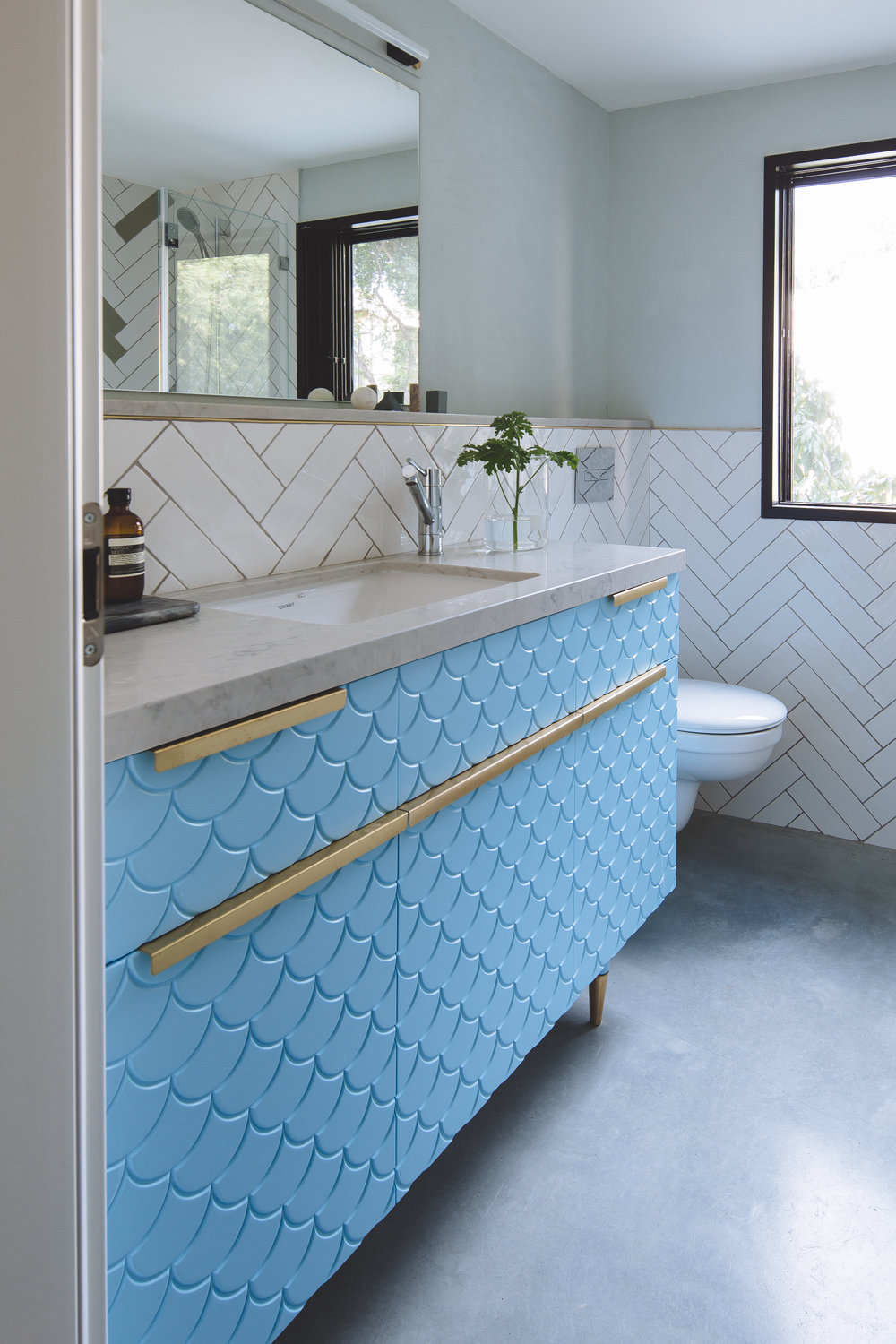 Blue bathroom cabinet. Concrete floor and brass details