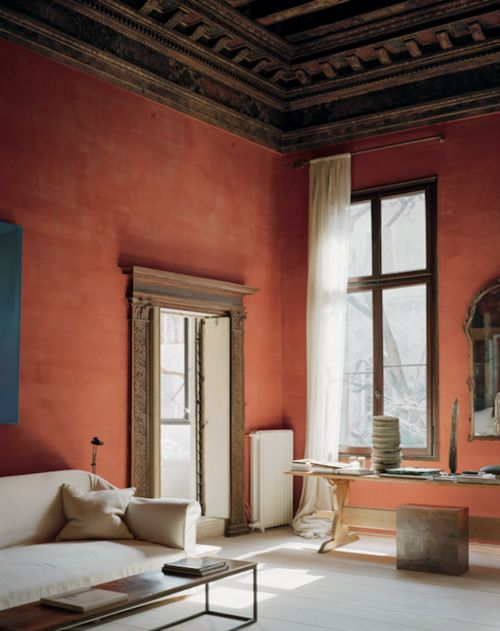 Orange walls and a classicist wood ceiling