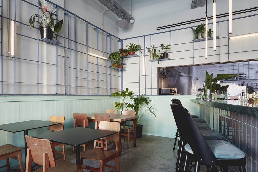 Restaurant design. concrete floor. mint color wall covering with metal grid element combined with tube lighting and plants.