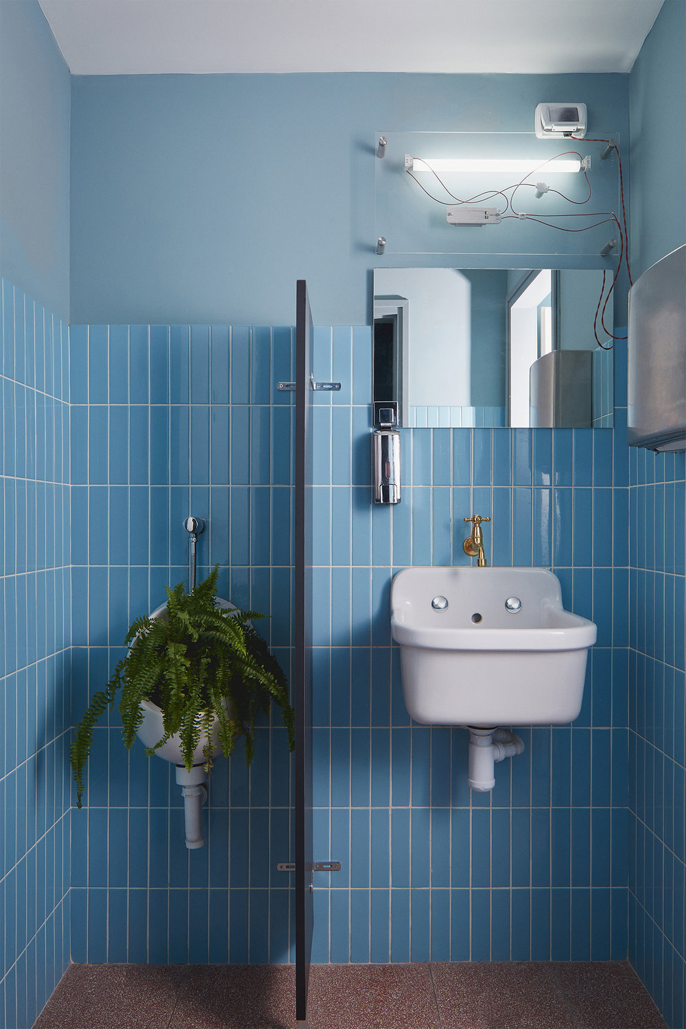 restaurants toilets with red terrazzo floor and light blue tiles. perspex light object
