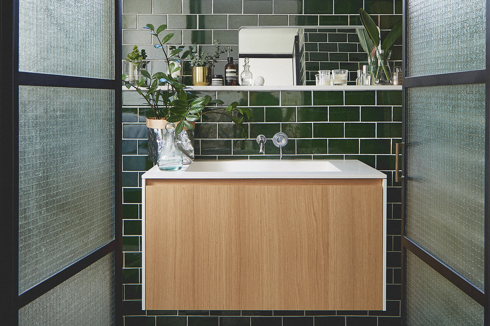 Steel frame doors bathroom emerald green tiles plants and cosmetics corian sink