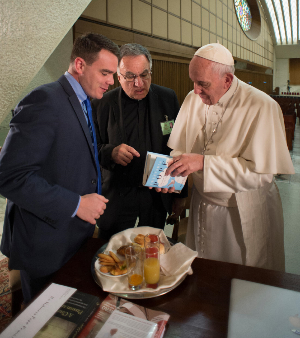 Pope Francis reads a copy of The Tweetable Pope, given to him by the author in October at the Vatican (Photo by Michael O'Loughlin)